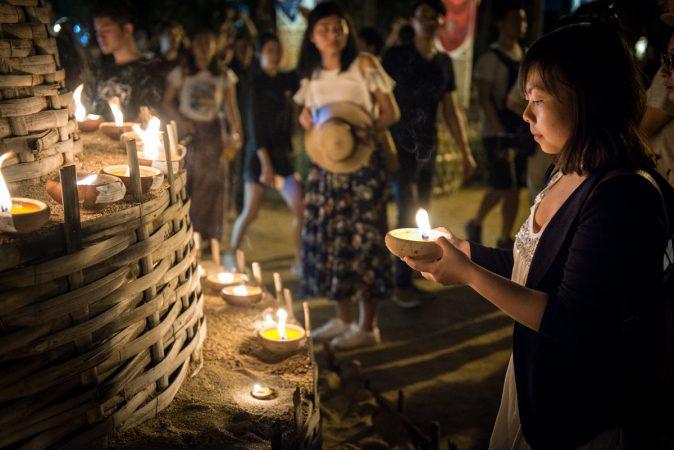 Frau mit Kerze an Thailändischem Tempel