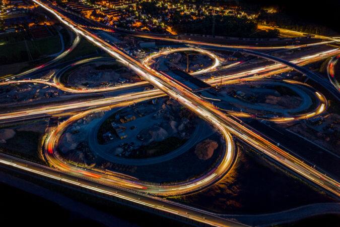 Langzeitbelichtung einer Autobahnkreuzung bei Nacht aus der Luft